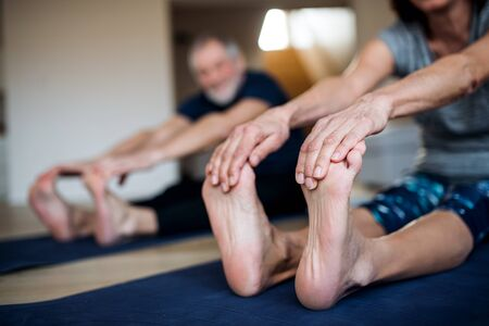Foto de A midsection of senior couple indoors at home, doing exercise on the floor. - Imagen libre de derechos
