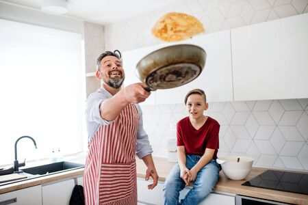 Foto de Mature father with small son indoors in kitchen, flipping pancakes. - Imagen libre de derechos