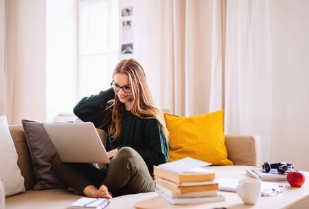 Photo for A young female student sitting on sofa, using laptop when studying. - Royalty Free Image