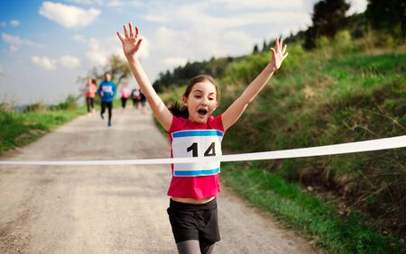 Foto de Small girl runner crossing finish line in a race competition in nature. - Imagen libre de derechos