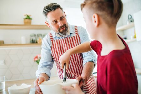 Photo pour Mature father with small son indoors in kitchen, making pancakes. - image libre de droit