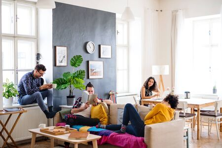 Photo pour A group of young friends relaxing indoors, house sharing concept. - image libre de droit