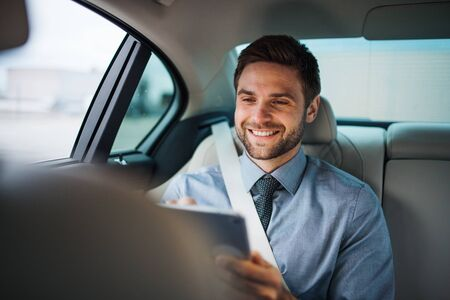 Businessman with tablet sitting on back seats in car, working.