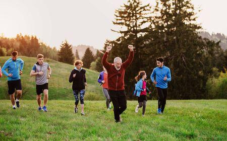 Foto de Large group of people cross country running in nature. - Imagen libre de derechos