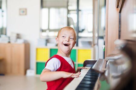 Foto de A down-syndrome school boy sitting at school, playing piano. - Imagen libre de derechos