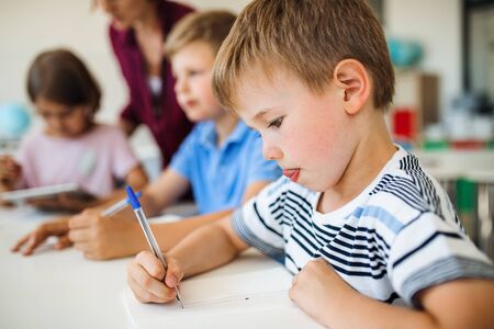 Photo pour A group of small school kids with teacher in class writing. - image libre de droit