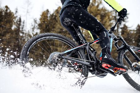Photo pour Midsection of mountain biker riding in snow outdoors in winter. - image libre de droit