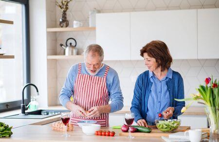 Photo pour A portrait of senior couple indoors at home, cooking. - image libre de droit