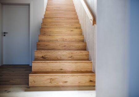 Photo pour A wooden staircase and white wall in an interior of a house. - image libre de droit