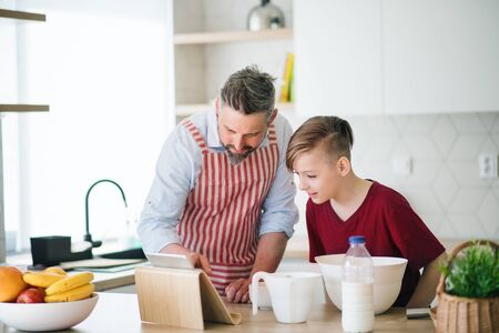 Photo pour Mature father and small son with tablet indoors in kitchen, making pancakes. - image libre de droit