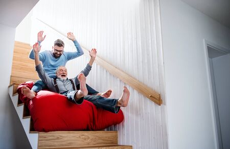 Photo for An adult hipster son and senior father indoors at home, having fun. - Royalty Free Image