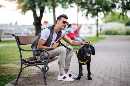 Photo pour Young blind man with white cane and guide dog sitting in park in city. - image libre de droit