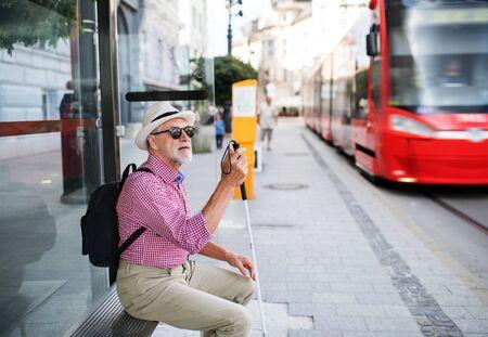 Photo pour Senior blind man with white cane waiting for public transport in city. - image libre de droit