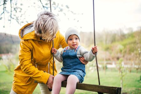 Photo pour Senior grandmother with toddler granddaughter on a swing in garden in spring. - image libre de droit