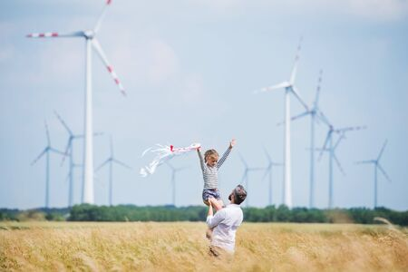 Foto de Mature father with small daughter standing on field on wind farm. - Imagen libre de derechos