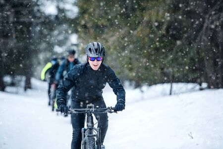 Foto de Group of mountain bikers riding on road outdoors in winter. - Imagen libre de derechos