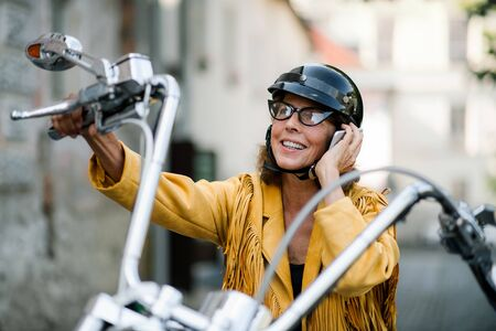 Photo pour Cheerful senior woman traveller with motorbike in town, making phone call. - image libre de droit