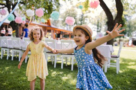 Photo pour Small girls running outdoors in garden in summer, birthday celebration concept. - image libre de droit