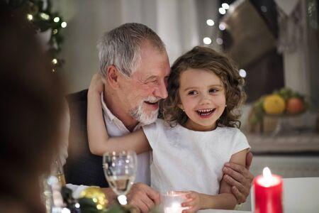 Foto de Senior grandfather with small granddaughter indoors at Christmas, sitting at table. - Imagen libre de derechos