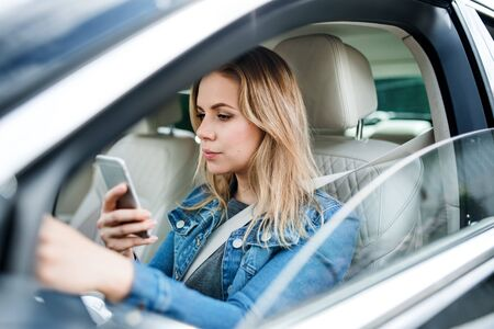 Photo for A young woman driver sitting in car, using smartphone. - Royalty Free Image