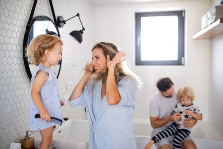 Foto de Young family with two small children indoors in bathroom, having fun. - Imagen libre de derechos