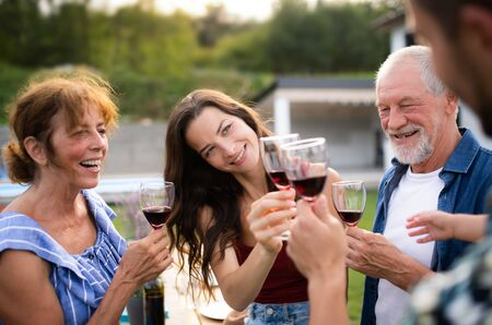 Photo pour Portrait of people with wine outdoors on family garden barbecue. - image libre de droit
