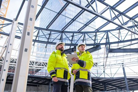 Photo for Men engineers standing outdoors on construction site, using tablet. - Royalty Free Image