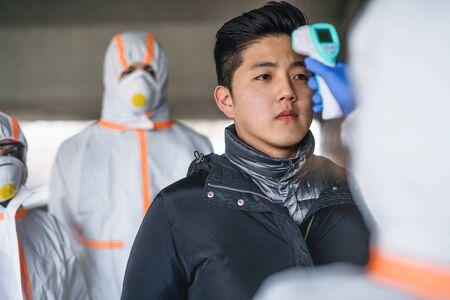 Photo pour People with protective suits helping man outdoors, coronavirus concept. - image libre de droit
