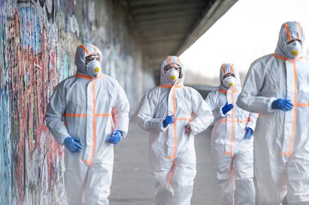 Photo pour People with protective suits and respirators running outdoors, coronavirus concept. - image libre de droit