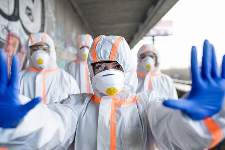 Foto de People with protective suits and respirators outdoors, coronavirus concept. - Imagen libre de derechos