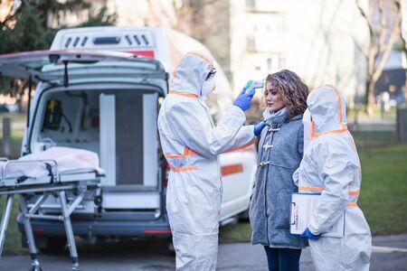 Photo pour People with protective suits helping woman outdoors, coronavirus concept. - image libre de droit