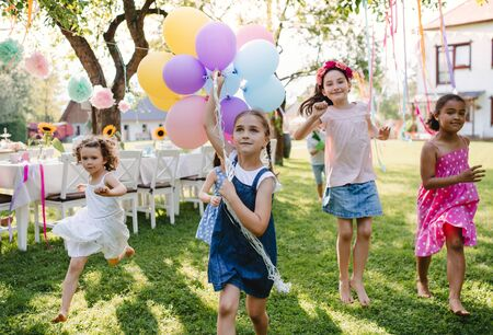 Photo pour Small children outdoors in garden in summer, playing with balloons. - image libre de droit