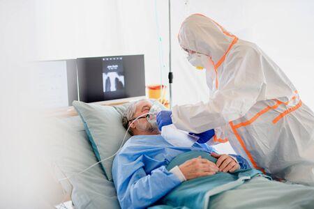 Foto de Infected patient in quarantine lying in bed in hospital, coronavirus concept. - Imagen libre de derechos
