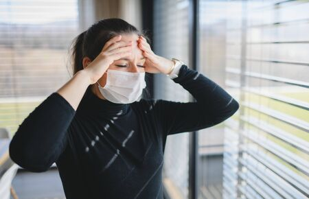 Photo pour Woman with headache and face masks indoors at home, Corona virus concept. - image libre de droit