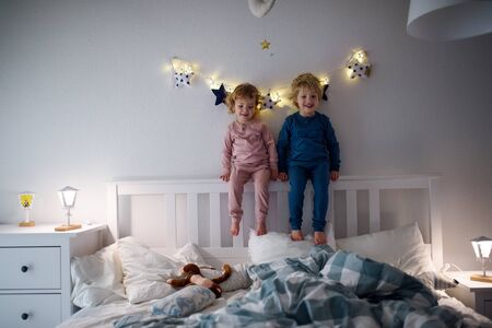 Photo for Two small children playing on bed indoors at home, having fun. - Royalty Free Image