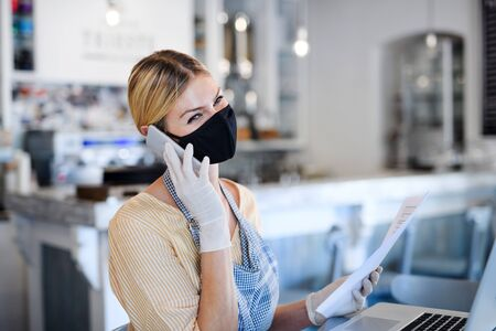 Photo for Coffee shop woman owner working with face mask, open after lockdown quarantine. - Royalty Free Image
