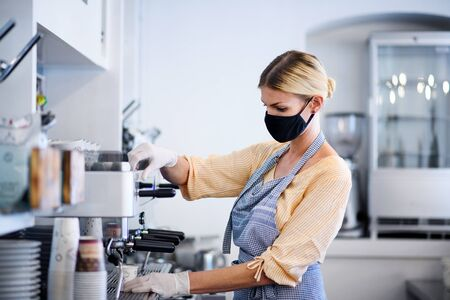 Foto de Coffee shop woman owner working with face mask, open after lockdown quarantine. - Imagen libre de derechos
