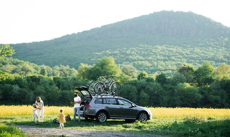 Foto de Family with two small children and face masks going on cycling trip in countryside. - Imagen libre de derechos