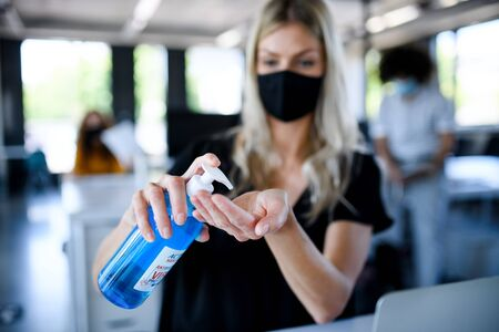 Photo pour Young woman with face mask back at work in office after lockdown, disinfecting hands. - image libre de droit