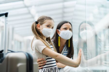 Photo pour Mother with daughter going on holiday, wearing face masks at the airport. - image libre de droit