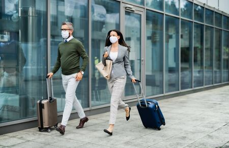 Photo pour Businesspeople with luggage going on business trip, wearing face masks at the airport. - image libre de droit