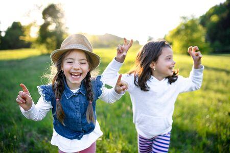 Foto für Portrait of two small girls standing outdoors in spring nature, laughing. - Lizenzfreies Bild
