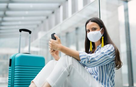 Photo pour Young woman with smartphone going on holiday, wearing face masks at the airport. - image libre de droit