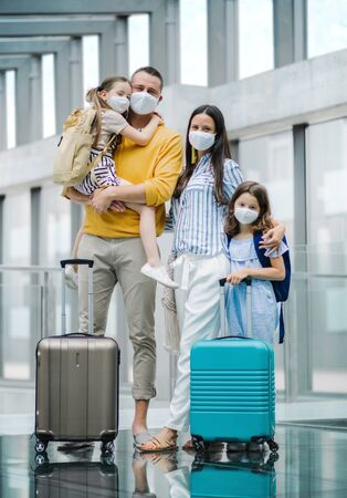 Photo pour Family with two children going on holiday, wearing face masks at the airport. - image libre de droit