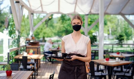 Photo for Waitress with face mask serving customers outdoors on terrace restaurant. - Royalty Free Image