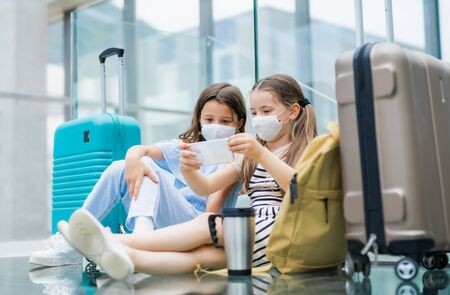 Photo pour Small children with smartphone going on holiday, wearing face masks at the airport. - image libre de droit