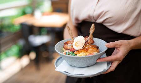 Photo pour Unrecognizable waitress with plate standing on terrace restaurant, midsection. Copy space. - image libre de droit