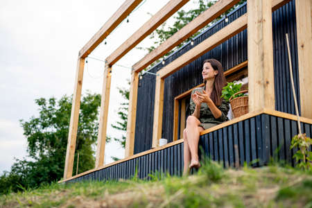 Photo pour Young woman with smartphone outdoors, weekend away in container house in countryside. - image libre de droit