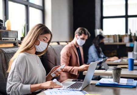 Foto de Portrait of young businesspeople with face masks working indoors in office, disinfecting laptop. - Imagen libre de derechos