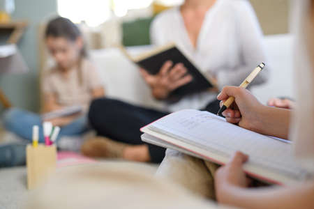 Foto de Group of homeschooling children with teacher studying indoors, coronavirus concept. - Imagen libre de derechos